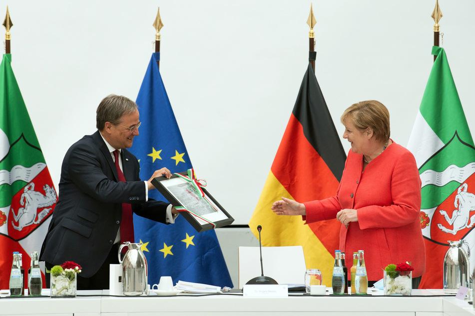 Bundeskanzlerin Angela Merkel (CDU) bekommt von Armin Laschet (CDU), Ministerpräsident von Nordrhein-Westfalen, ein Luftbild von Templin als Geschenk der Landesregierung.