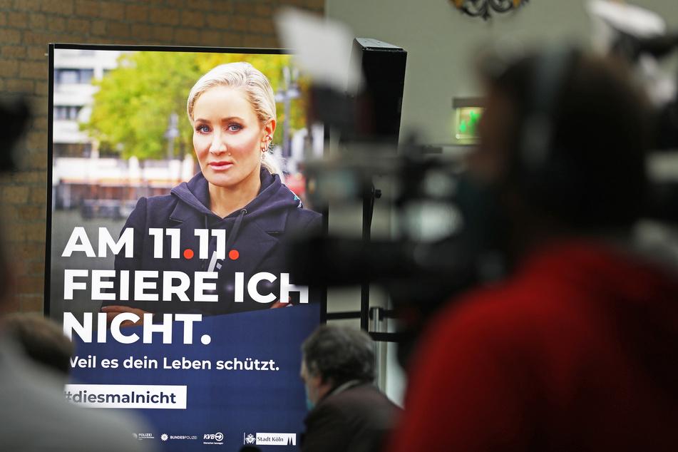 """Hinter Kameraleuten ist ein Werbeplakat mit Schauspielerin und Moderatorin Janine Kunze und der Aufschrift: """"Am 11.11. feiere ich nicht"""" zu sehen."""