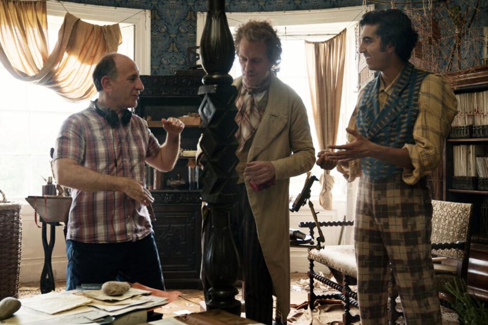Regisseur Armando Iannucci (l.) gibt Hugh Laurie (M., Mr. Dick) und Dev Patel (David Copperfield) am Filmset Anweisungen für die nächste Szene.