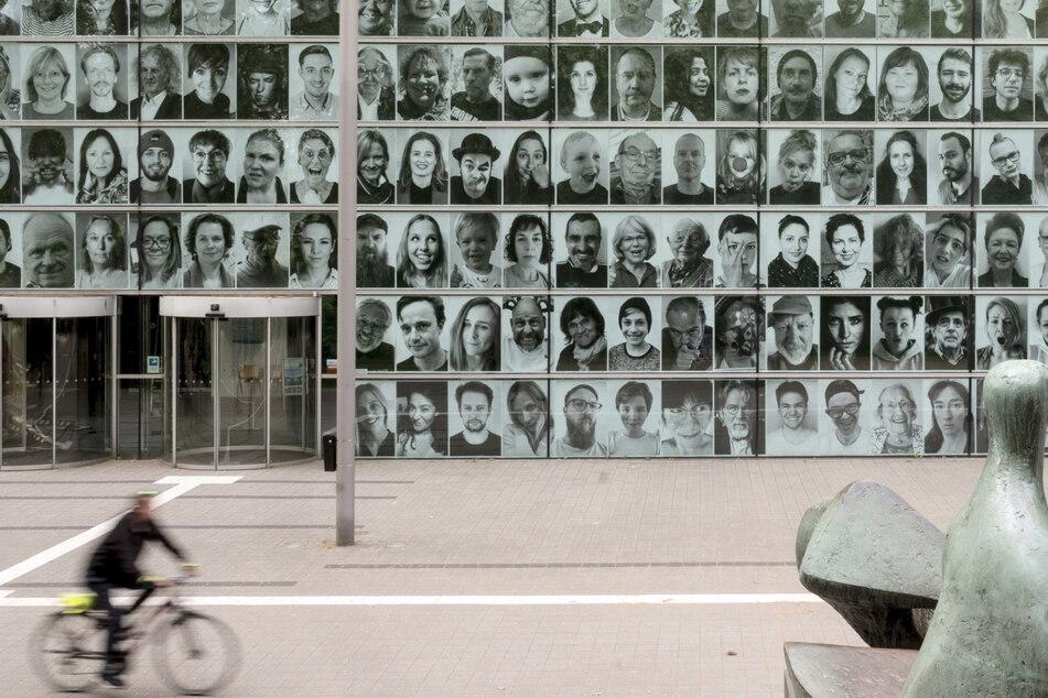 """An der Fassade des Ruhrfestspielhauses hängen großformatige Fotos von Menschen, die eigentlich in diesen Wochen bei dem renommierten Theatertreffen zusammengekommen wären. Besucher wie Kunstschaffende haben aus der Isolation Porträtfotos schicken, die dann Teil des """"Inside Out Projects"""" des französischen Künstlers JR geworden sind."""