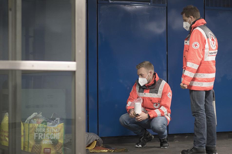 Die Rettungssanitäter Tobias (l.) und Martin sprechen mit einem Mann, der in einer Unterführung sitzt.
