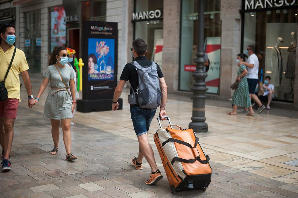 Spanien, Malaga: Ein Tourist trägt seine Taschen durch die Straße Marques de Larios.