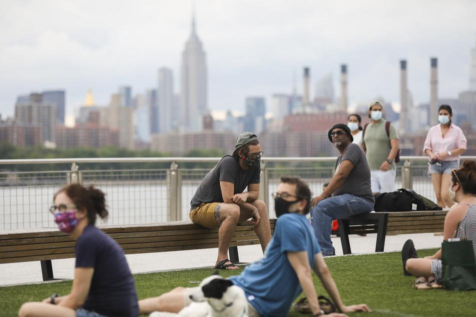 """Menschen, die zum Schutz vor der Verbreitung des Coronavirus Mundschutze tragen, sitzen im """"Domino Park"""" am Fluss """"East River""""."""