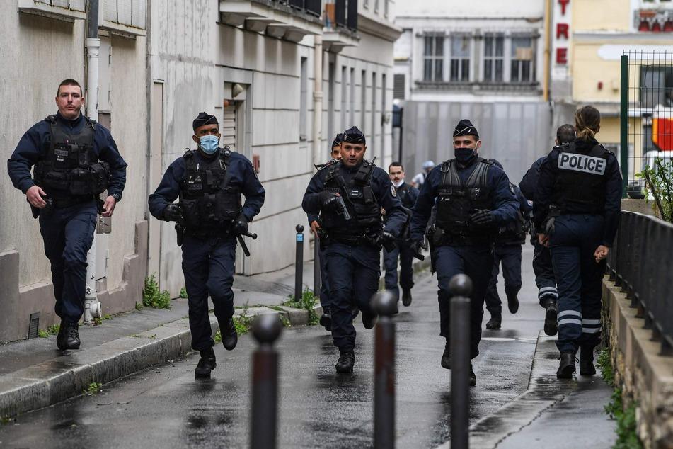 Französische Polizisten eilen zum Tatort, nachdem in der Nähe der ehemaligen Büros des französischen Satiremagazins Charlie Hebdo nach einem angeblichen Angriff eines Mannes mit einem Messer.