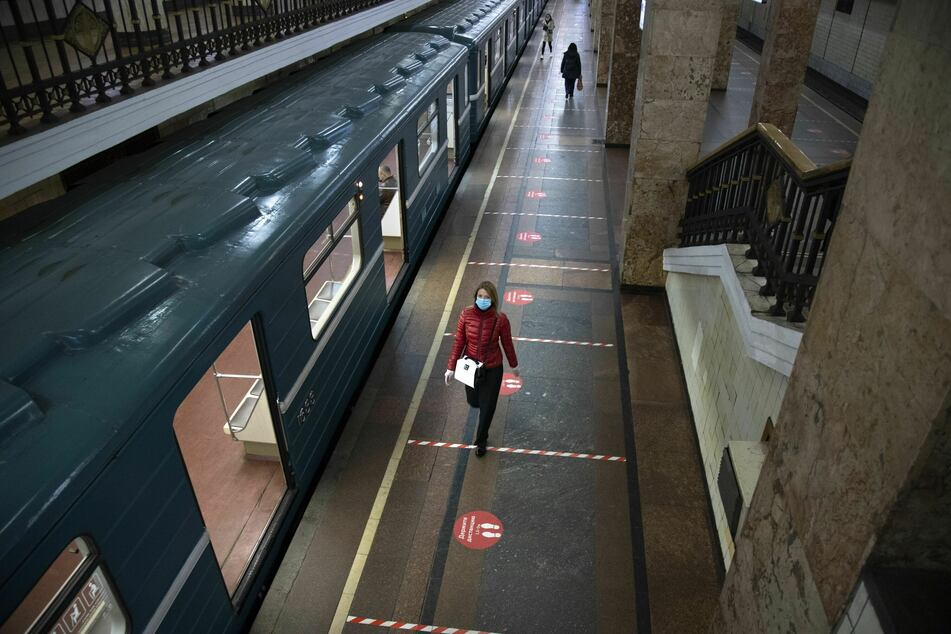 Reisende mit medizinischen Mundschutzmasken gehen am Gleis eines U-Bahnhofs entlang. Seit dem 12.05.2020 ist das Tragen von Gesichtsmasken und Latexhandschuhen für Personen, die die öffentlichen Verkehrsmittel in Moskau benutzen, Pflicht.