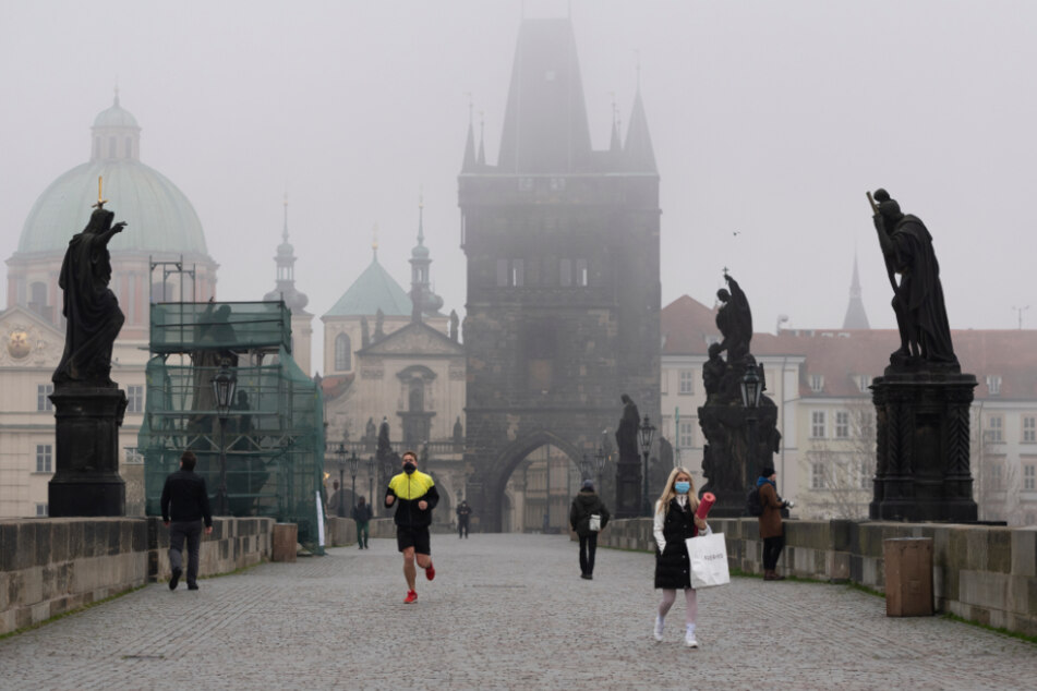 Nebel liegt über der Karlsbrücke, über die nur wenige Passanten gehen.