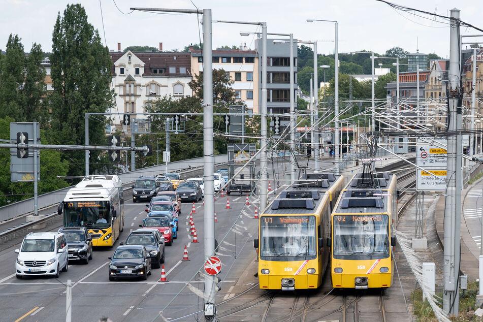 Zwei Stadtbahnen fahren neben Autos und einem Bus.