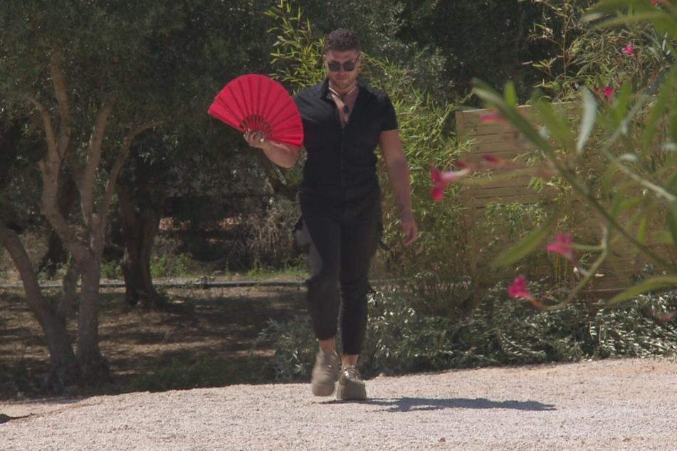 David (24) aus Köln erschien top-gestylt mit rosa Fächer.
