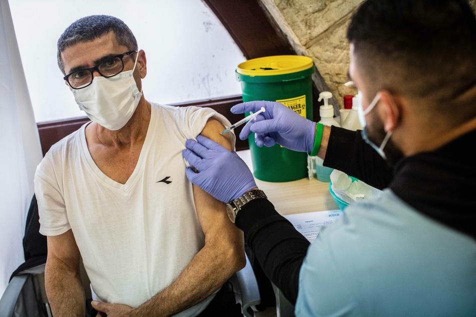 Ein Mann erhält von einem medizinischem Mitarbeiter in einem Impfzentrum in Jerusalem eine Impfung gegen das Coronavirus.