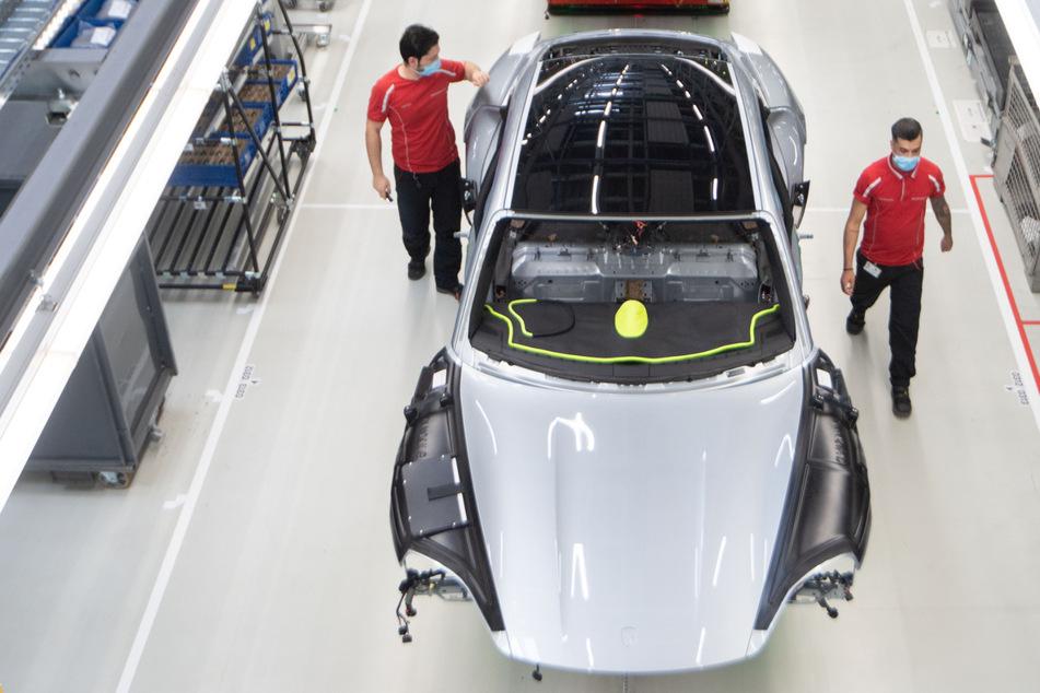 Mitarbeiter der Porsche AG haben in der Produktion des batterieelektrische angetriebenen Sportwagens Porsche Taycan einen Mundschutz an.