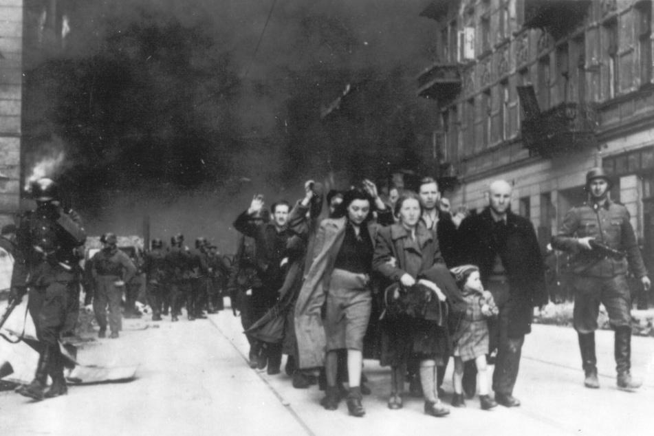 Auf dem Foto aus dem Jahr 1943 wird eine Gruppe polnischer Juden während der Zerstörung des Warschauer Ghettos durch deutsche Truppen zur Deportation durch deutsche SS-Soldaten abgeführt.