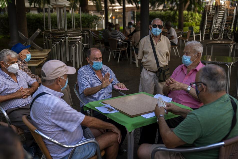 Rentner mit Mundschutz spielen in einem Park auf der Insel Gran Canaria Karten.
