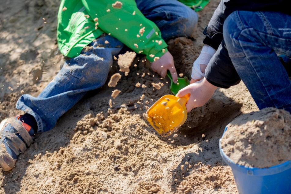 Zwei Kinder spielen in einer Kita mit Sand. (Symbolbild)