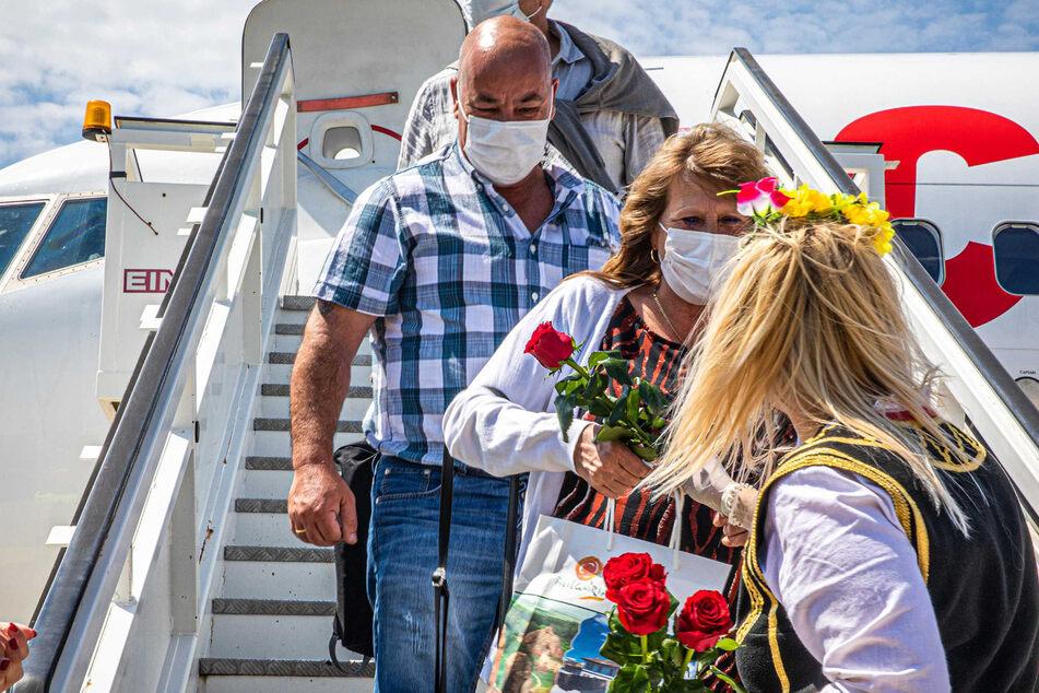 Niederländische Urlauber werden am Flughafen mit Rosen begrüßt. (Archivbild)