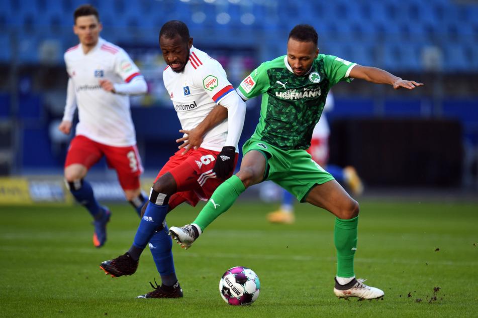 HSV-Mittelfeldspieler David Kinsombi (M.) und Greuther Fürths Julian Green kämpfen um den Ball.