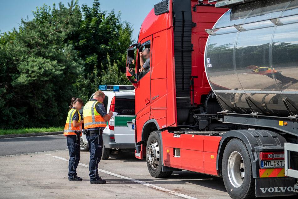 Die Zöllner befragen einen Lkw-Fahrer nach seinen Beschäftigungsverhältnissen.