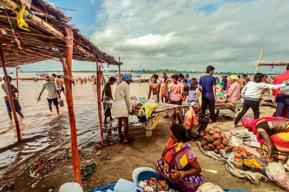 Rising river levels cause people to move possessions in Prayagraj district, India.