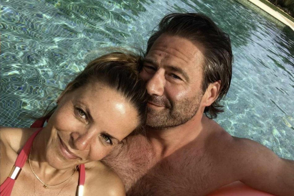 Sasha (49) und seine Frau Julia Röntgen (37) genießen in einem Pool die Sonne.