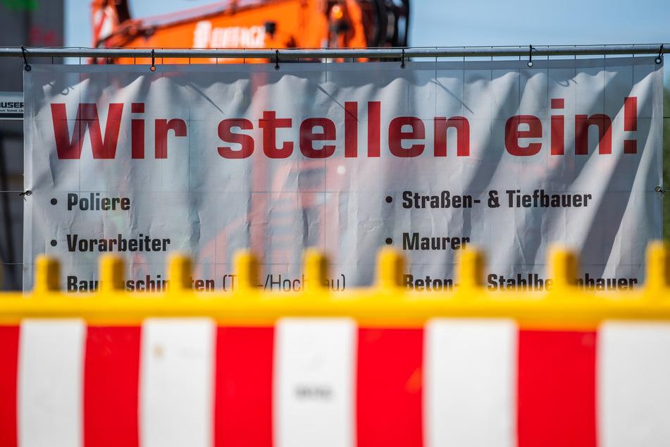 """An einem Bauzaun einer Baustelle hängt ein Banner mit der Aufschrift """"Wir stellen ein!""""."""