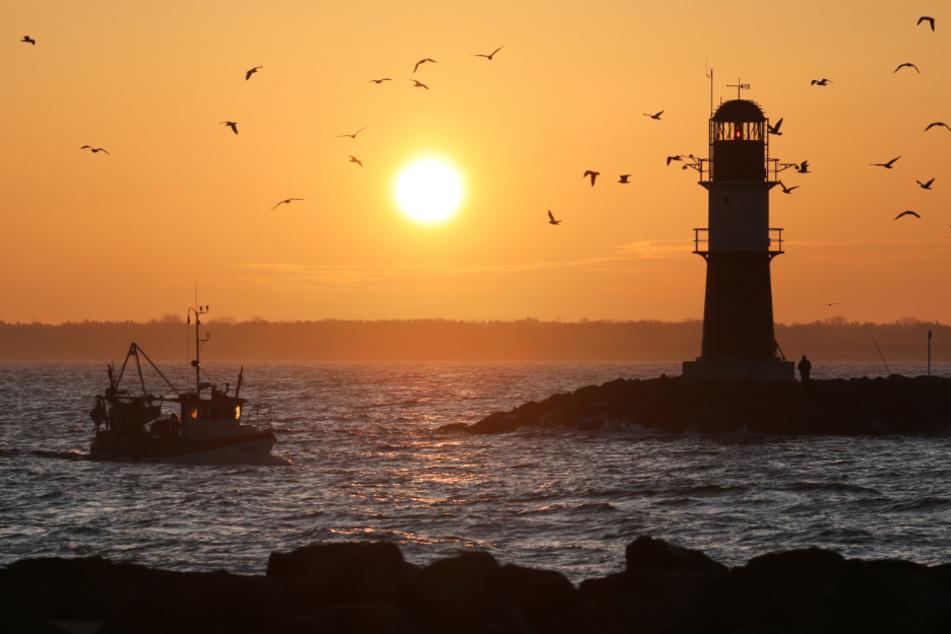 Romantik pur an der Ostsee: Die Sonne geht auf, ein Fischer kommt zurück in den Hafen von Warnemünde.