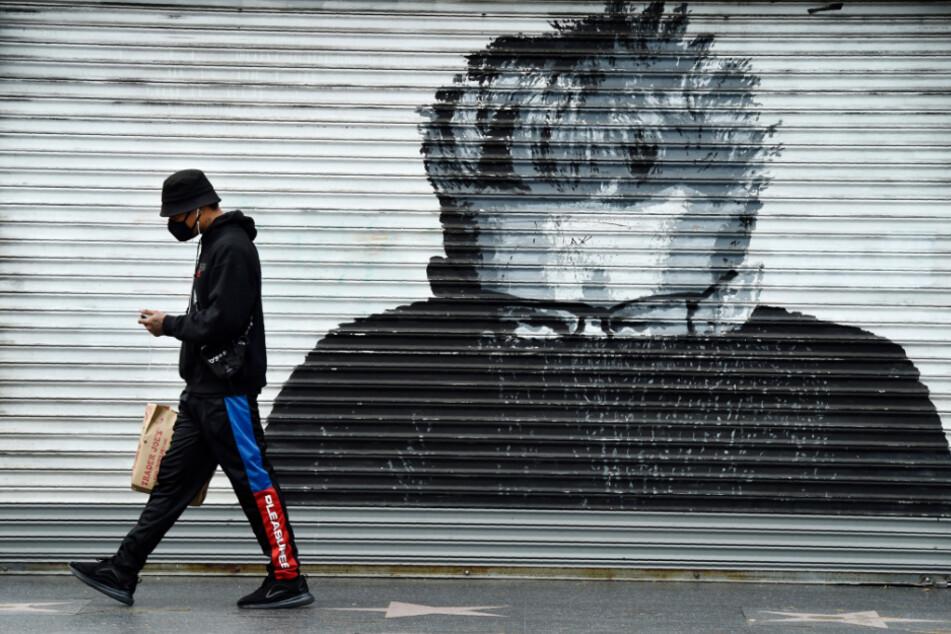 USA, Los Angeles: Ein Mann trägt eine Maske, während er an einem geschlossenen Schaufenster mit dem Konterfei des Schauspielers James Dean auf dem Hollywood Walk of Fame vorbeigeht.