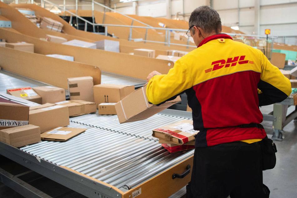 Ein Paketbote bei der Arbeit in einem DHL-Verteilzentrum. In Berlin soll ein Zusteller unter falschem Namen Pakete bestellt und anschließend beiseite geschafft haben. (Symbolfoto)