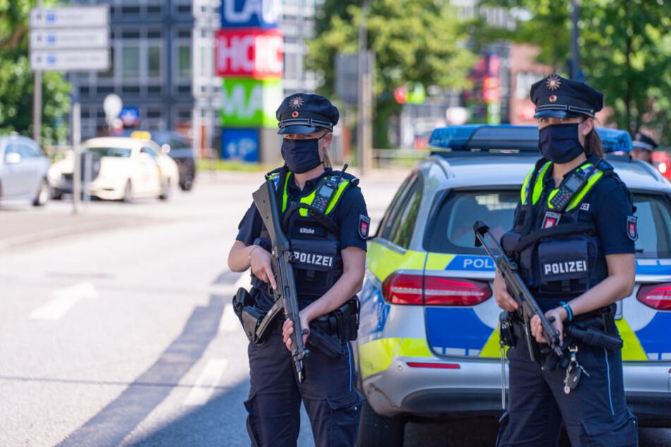 Zwei schwer bewaffnete Polizistinnen sichern die Gegen um den Tatort in Hamburg-Langenhorn.