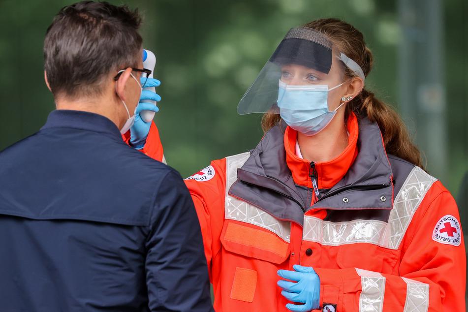 Eine Mitarbeiterin des Deutschen Roten Kreuzes (DRK) misst die Körpertemperatur eines Mannes.
