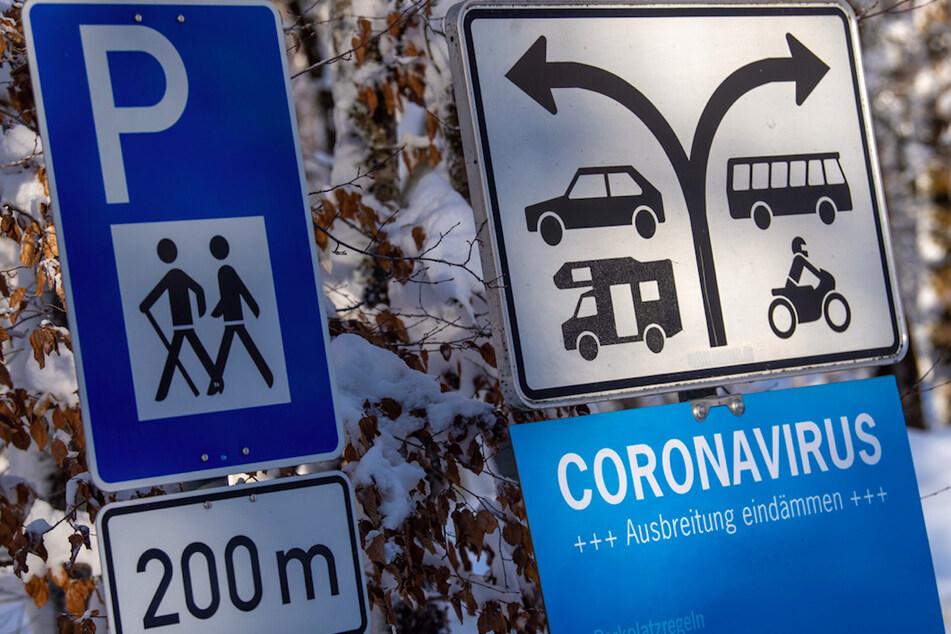 """Ein verschneites Schild mit der Aufschrift """"Coronavirus - Ausbreitung eindämmen"""" steht am Parkplatz von Schloss Linderhof."""