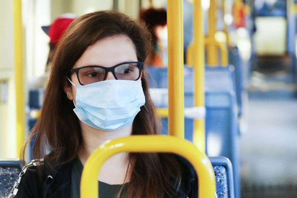 Eine Frau sitzt mit einer Maske in einer Tram.