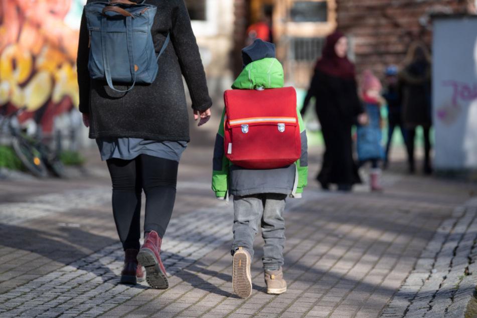 Eine Frau geht mit ihrem Kind vor einer Schule auf einem Weg.