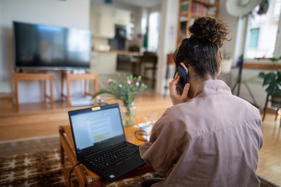 Eine junge Frau, die aufgrund der Corona-Pandemie im Homeoffice arbeitet, nimmt in ihrem Wohnzimmer an einer Telefonkonferenz teil.