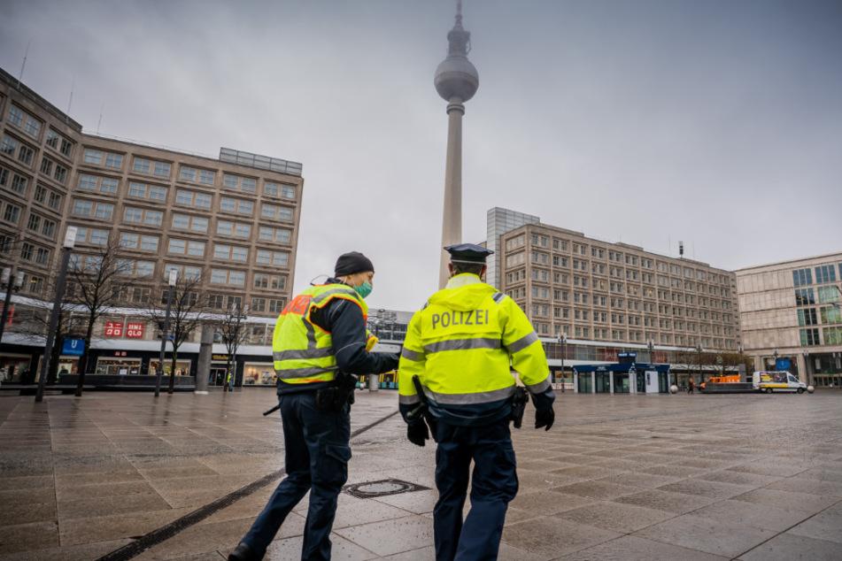 Zwei Polizisten laufen über den Alexanderplatz.