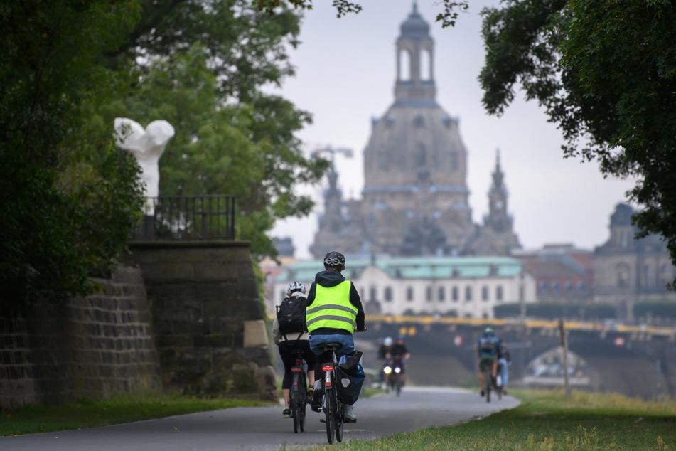 Radfahrer genießen das frühlingshafte Wetter in Dresden.