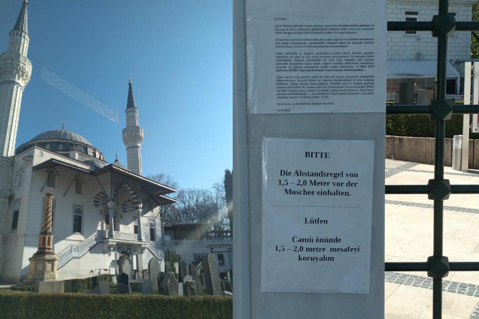 Ein zweisprachiger Hinweis weist vor der Sehitlik Moschee am Columbiadamm auf die Abstandsregel hin. (Bildmontage)