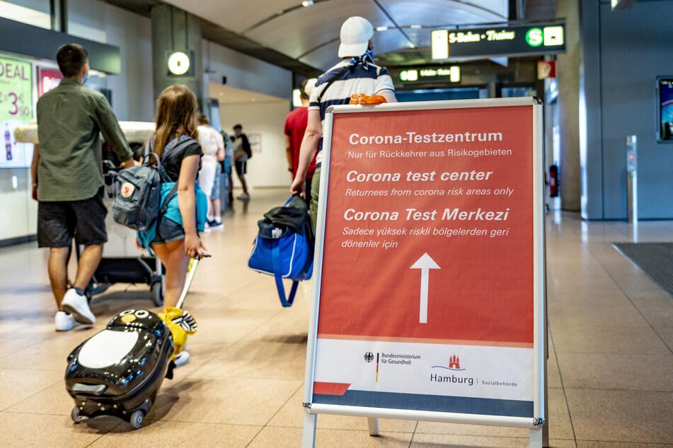 Reisende gehen aus dem Sicherheitsbereich des Hamburger Flughafens an einem Schild vorbei, auf dem die Richtung zum Corona-Testzentrum mit einem Pfeil angezeigt wird.