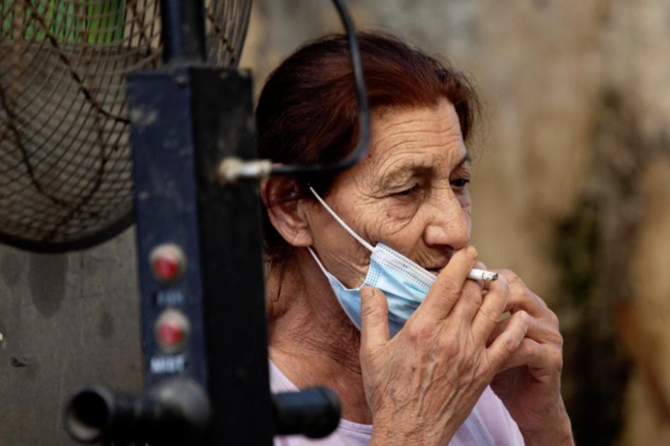 Israel, Ramla: Eine Frau nimmt ihre Gesichtsmaske ab und raucht eine Zigarette auf einem Lebensmittelmarkt. (Archivbild)