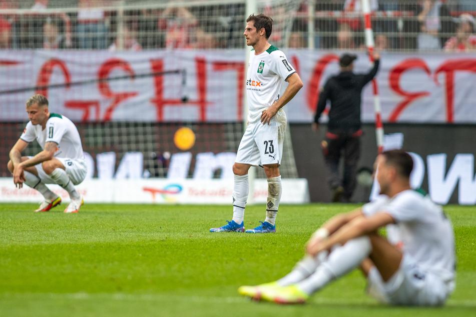 Jonas Hofmann (M.) steht enttäuscht auf dem Spielfeld, während seine Kollegen Jordan Beyer (21, l.) und Ramy Bensebaini (26) konsterniert zu Boden gegangen sind.