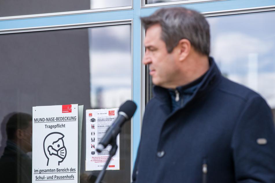 """""""Mund-Nase-Bedeckung Tragepflicht"""" steht auf einem Plakat am Sigena-Gymnasium neben Markus Söder (CSU), Ministerpräsident von Bayern, der nach dem Besuch einer Teststation für Corona-Schnelltests in der Schule zu Journalisten spricht."""