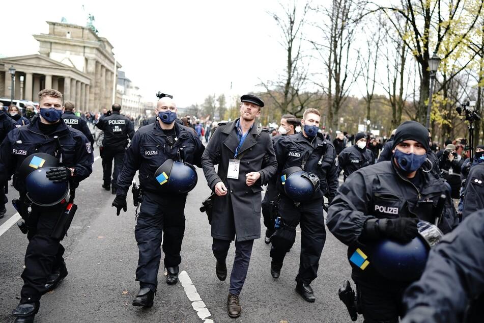 """Der rechtsextreme Aktivist Nikolai Nerling, bekannt als Videoblogger """"Der Volkslehrer"""" wird vor dem Brandenburger Tor von der Polizei abgeführt."""