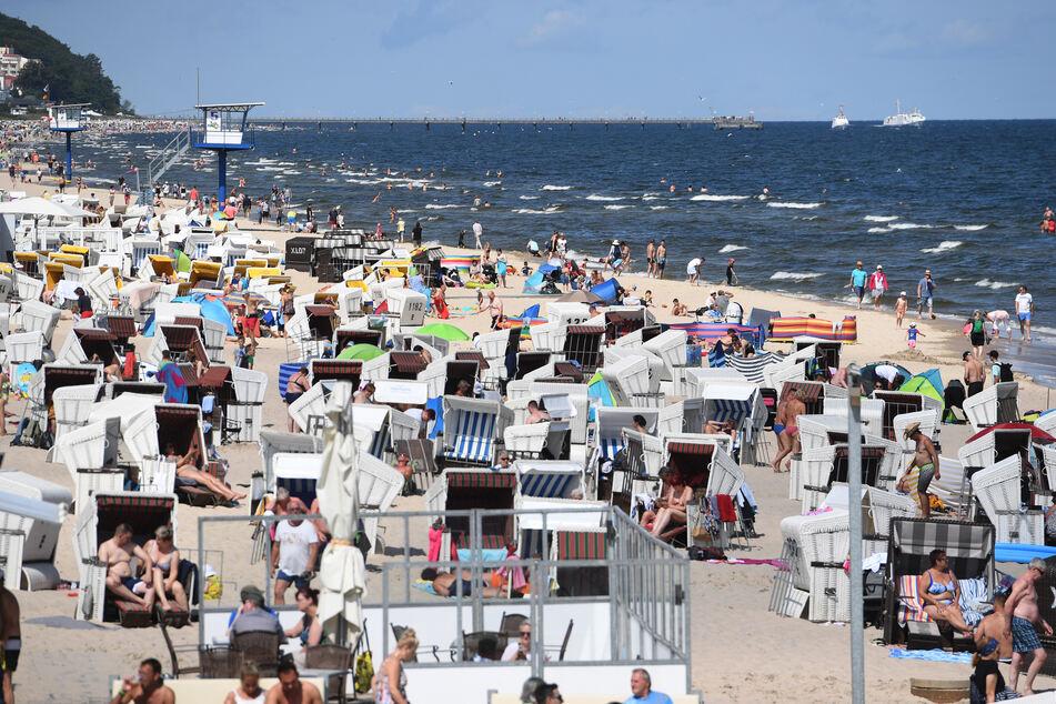 Touristen nutzen das hochsommerliche Wetter am Strand auf der Insel Usedom zum Sonnen und Baden.