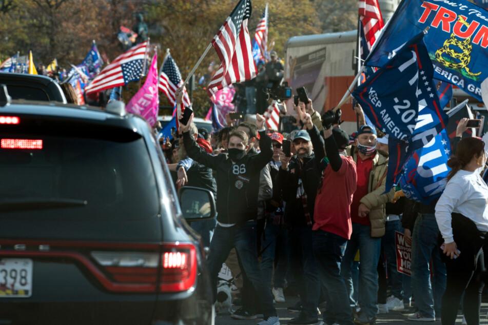 Der US-Präsident Trump fährt in einer Autokolonne an einer Gruppe von Anhängern vorbei, die zu dessen Unterstützung und gegen angeblich gefälschte Wahlergebnisse in der Nähe des Weißen Hauses demonstrieren.