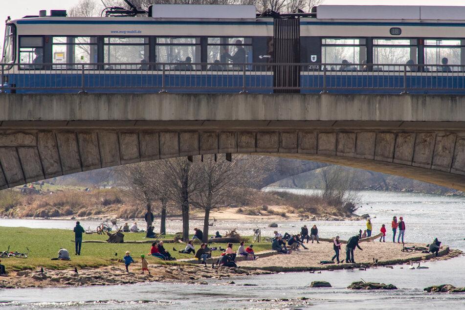 Passanten halten sich am Ufer der Isar auf, während eine Trambahn über die Reichenbachbrücke in München fährt.