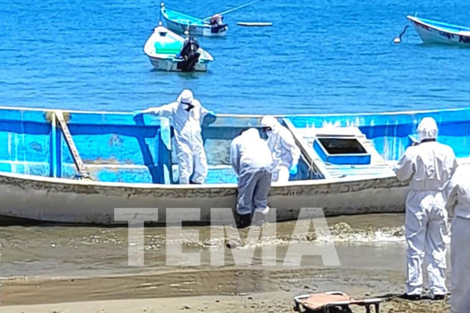 Ermittler untersuchen das Boot mit den gefundenen Leichen.