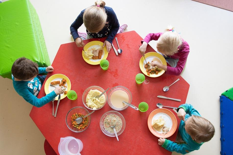Kinder sitzen im Rahmen der Notbetreuung in einem Kindergarten während des Mittagessens an einem Tisch. (Symbolbild)