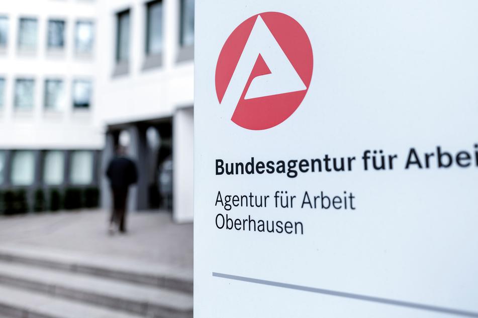 Ein Schild mit dem Symbol der Bundesagentur für Arbeit steht vor der Zweigstelle der Agentur.