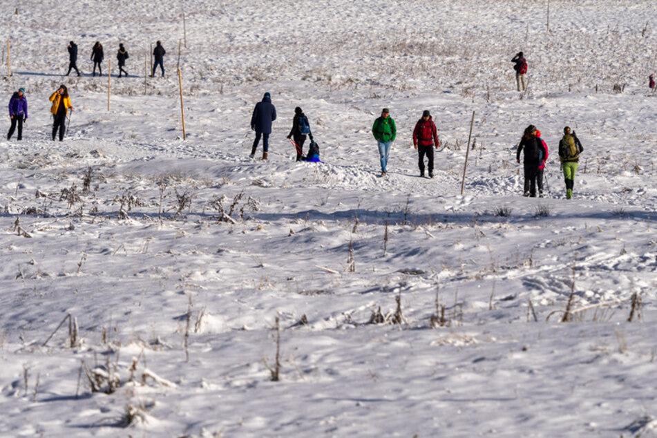 Besucher laufen durch den verschneiten Firstgraben am Spitzingsee, der 1084 Meter über dem Meer liegt.