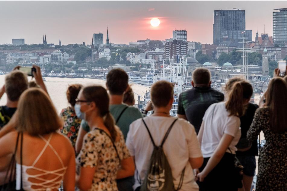 Besucher der Plaza der Elbphilharmonie betrachten den Sonnenuntergang im Westen Hamburgs.