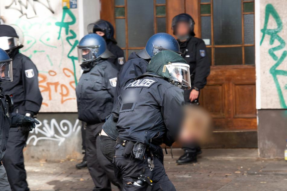 Polizeibeamte führen in der Weisestraße einen Mann ab.