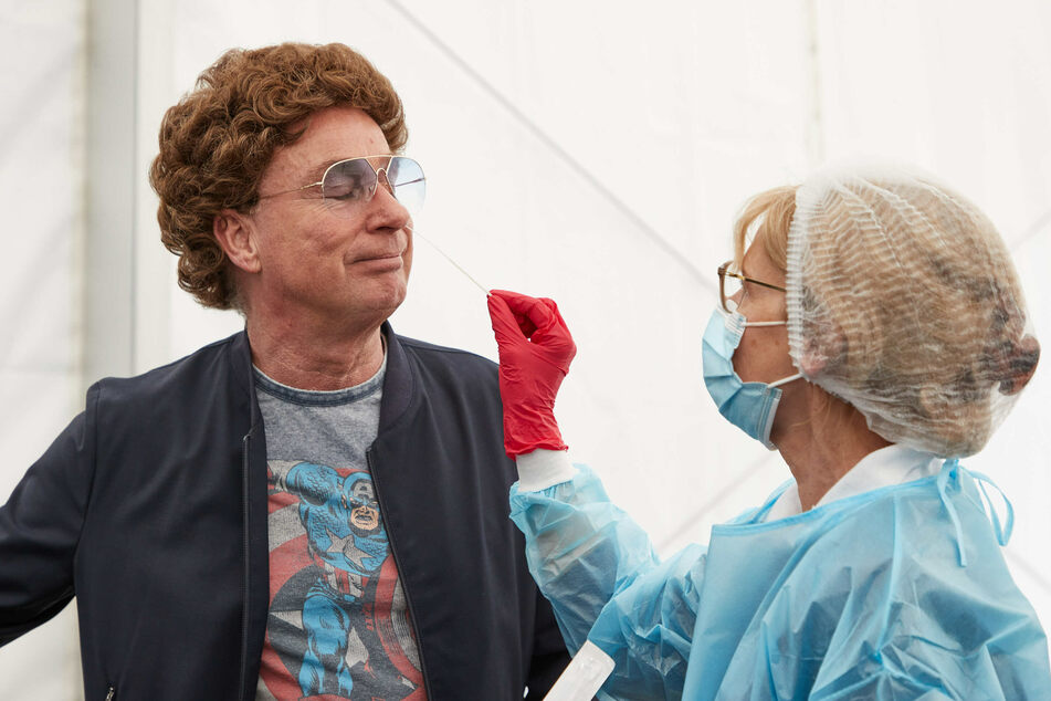 Atze Schröder lässt von Dr. Natasha Schlothauer, Testerin, im Drive-In-Testzentrum an der Barclaycard Arena bei einem Pressetermin einen Nasenabstrich an sich durchführen.